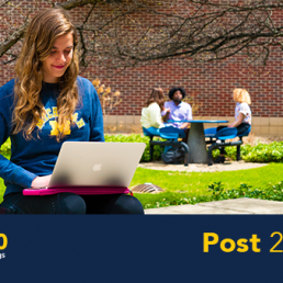 U-M student sitting on a bench working on a laptop