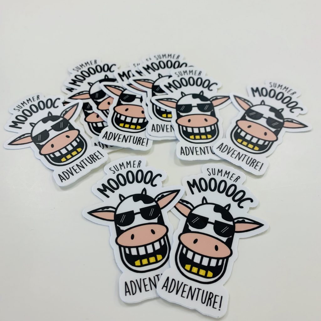 "Photo of an assortment of stickers with an illustration of a smiling cow with the words ""Summer MOOOOC Adventure."""