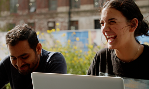 A male student on the left laughing with a female student on the right with her laptop open.