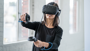 A woman wearing a virtual reality headset and holding two VR devices in her hand with one hand held higher than the other.