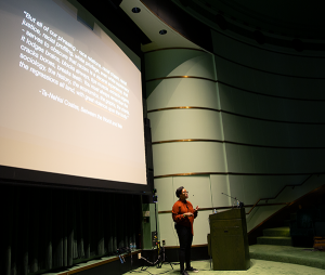 Dr. Courtney Cogburn speaking to an audience and standing in front of a large projection screen in a lecture hall.