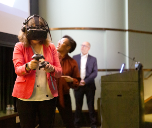 Rachel Niemer facing the camera wearing a VR headset and holding her arms out while Courtney Cogburn and Jeremy Nelson view a large projector screen behind her.