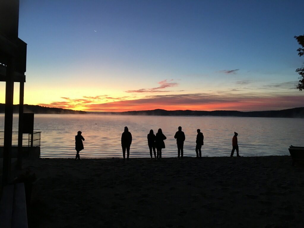 Students walking on the beach at sunset