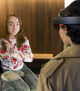 (Image of a person wearing a virtual reality headset sitting across from a virtually constructed person.)