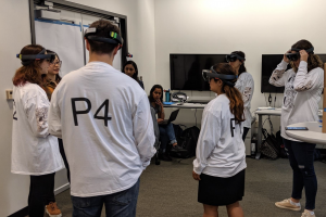 (A group of eight students, five of whom are wearing virtual reality headsets, standing in a circle in a classroom.)