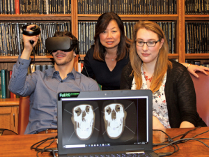 Group posed behind laptop as one person wears VR headset and laptop shows what person sees in VR