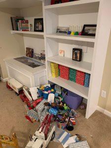 Toys on floor below bookcase