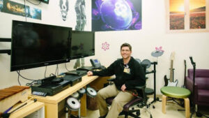 JJ Bouchard at a technology hub desk with video game system monitors, instruments and more
