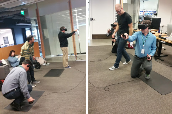 men testing out Oculus VR headsets in large room