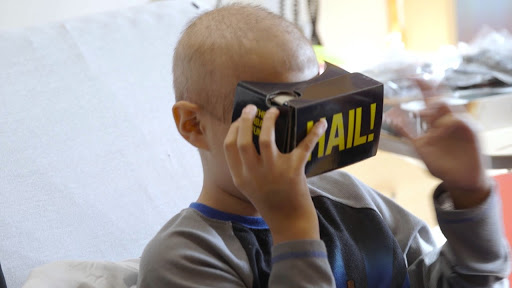CS Mott Children's Hospital patient wearing vr headset with HAIL! written on the headset