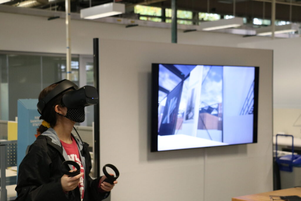 Student Caitlyn Chua with an XR headset on looking up
