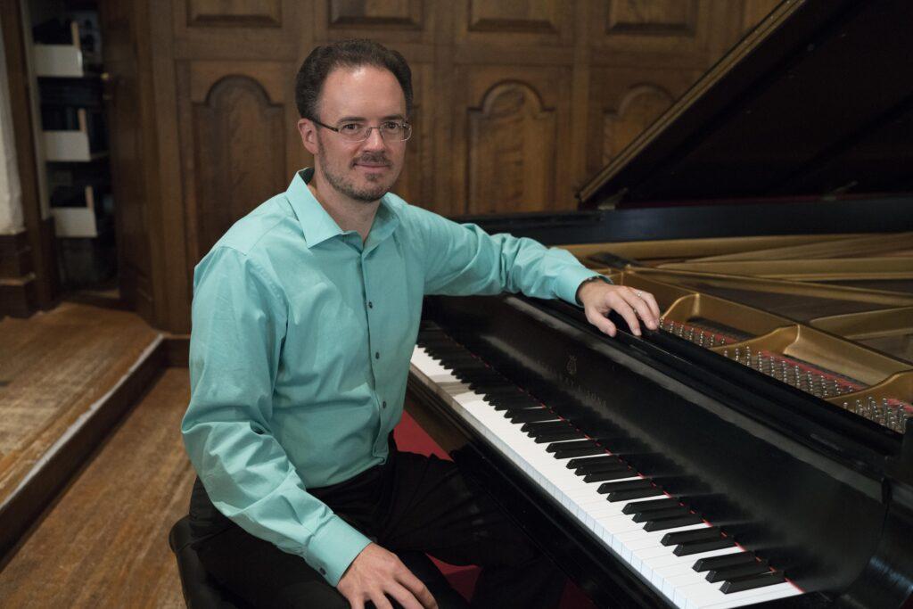 Matthew Bengtson poses while sitting at a piano