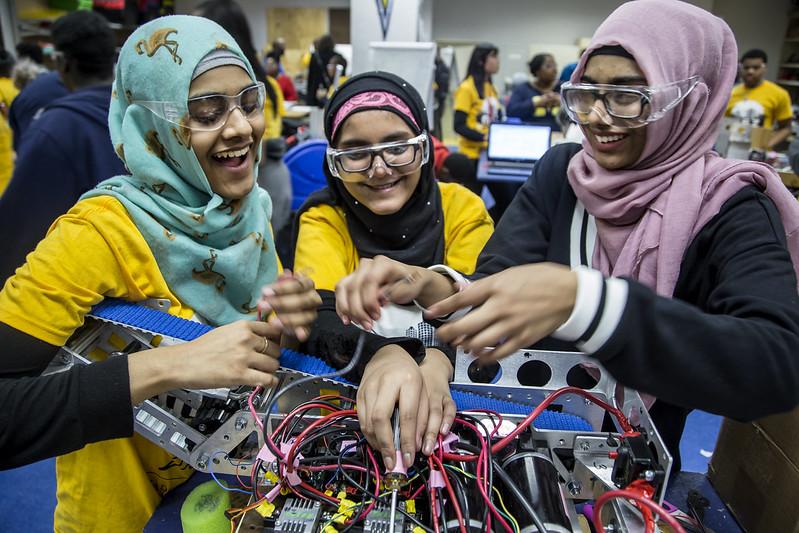 Three women working on a robotics projects