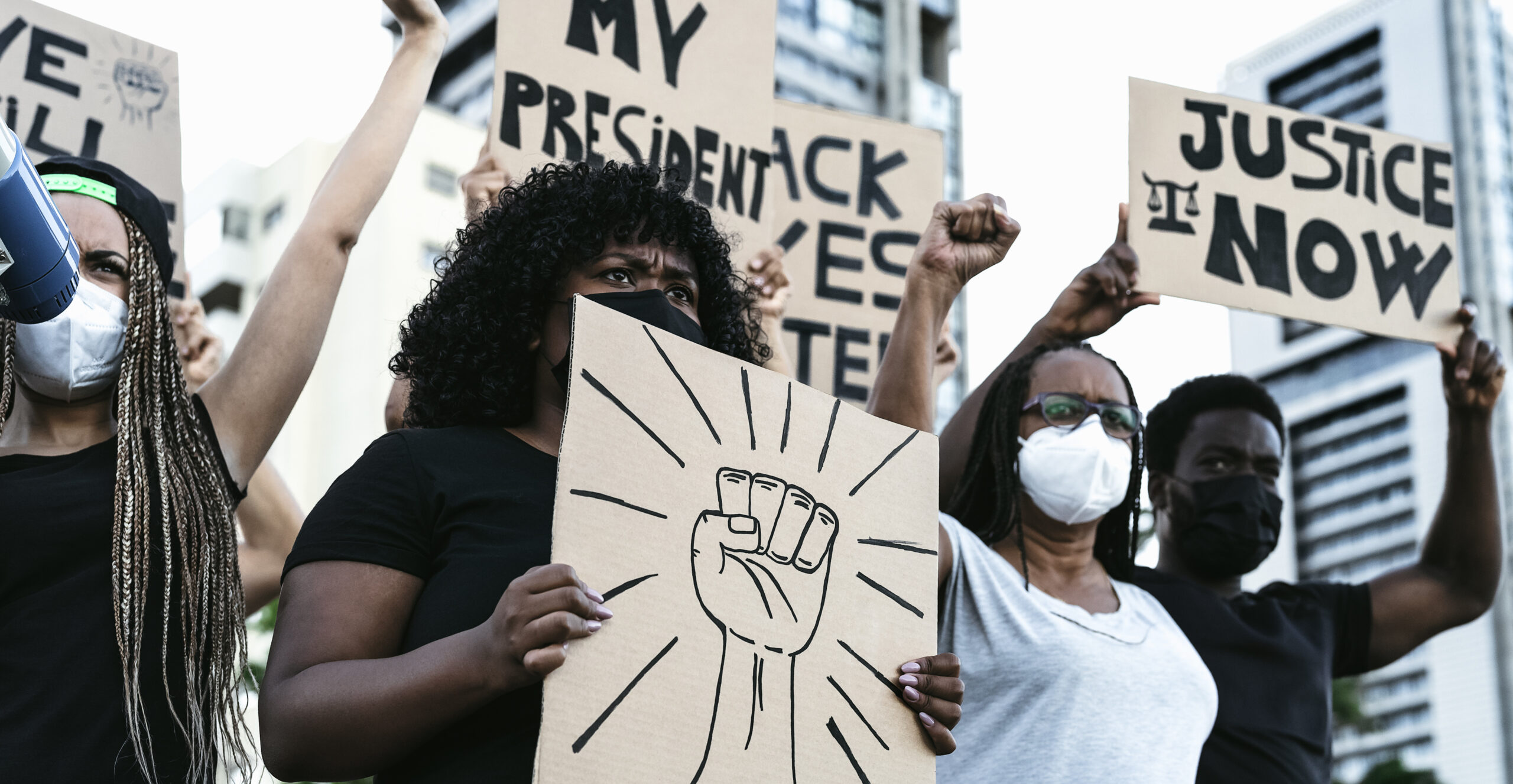 people in masks holding up signs support of black lives matter movement