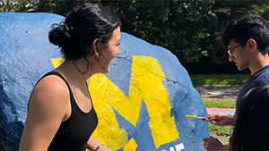Two students painting the rock with a michigan M