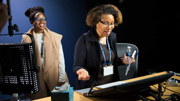 Two women engaging in a hands on experience within the Academic Innovation filming studios