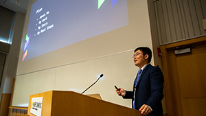 Xucong Zhen presenting at a podium with a presentation in the background