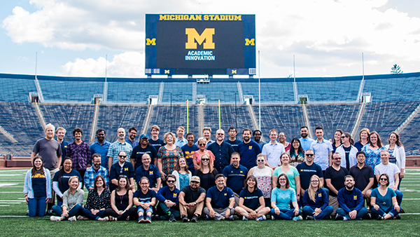 Photo of several individuals posing for the camera in the middle of Michigan Stadium with the Office of Academic Innovation logo on the jumbotron.