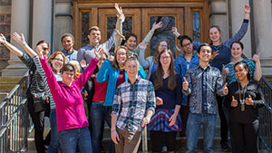 Group photo of Dr. Michaela Zint and her students posing with their hands in the air in front of an academic building