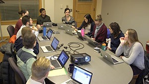 Students seated around a large table with laptops in discussion