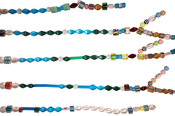 Five strands of varying styles of beads with branching strands attached to three of the five strands