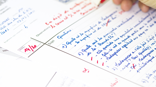 A hand grading a paper with red pen