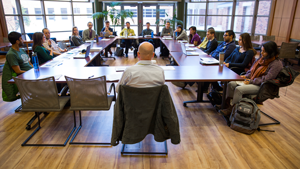 People sitting around a square conference room table