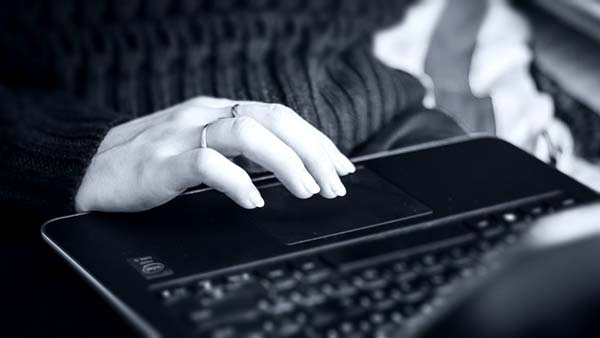Woman using trackpad on a laptop