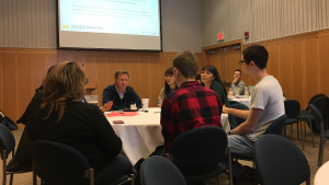 Students sitting around a table in discussion with edX and Academic Innovation representatives