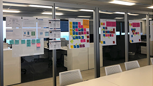 Large easel pages covered in multi-colored sticky notes adhered to glass walls in the Office of Academic Innovation
