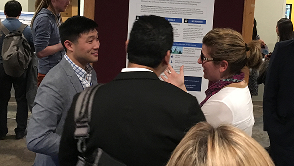 James Park speaking with two individuals in front of a poster