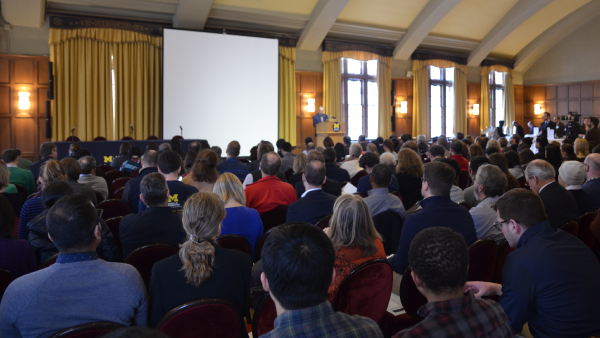 Large audience seated facing a podium in the Michigan League ballroom