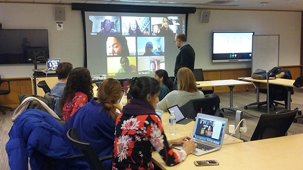Students seated around a long row of tables with professor Don Peurach standing at the front of room looking at a projection screen with seven individuals on webcams.