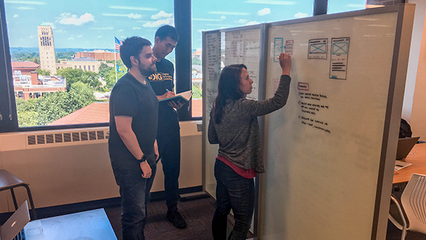 Three staff members collaborating around a white board with a view of campus in the background.
