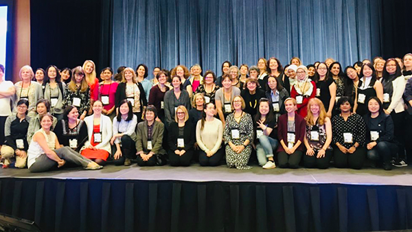 group of LAK attendees posing for a photo on stage for international womens day