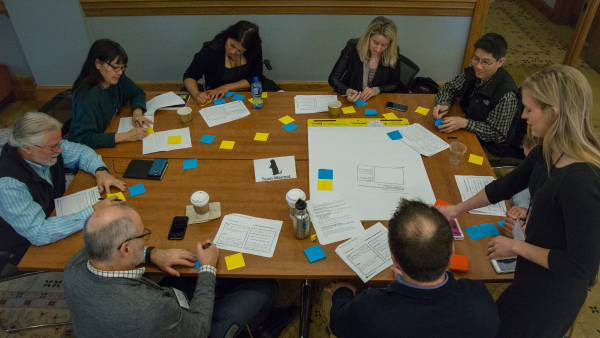 Individuals sitting around a table writing on sticky notes