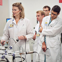 Instructor and students in lab coats