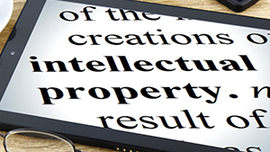 "Photo of a tablet with the words ""intellectual property"" on the screen"