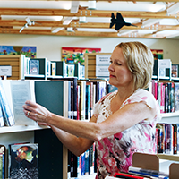 Woman placing books on a shelf in a library