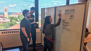 Three staff members collaborating around a white board with a view of campus in the background