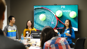 "Three students presenting to a large group in front of a screen with an image titled ""PR Tennis"""