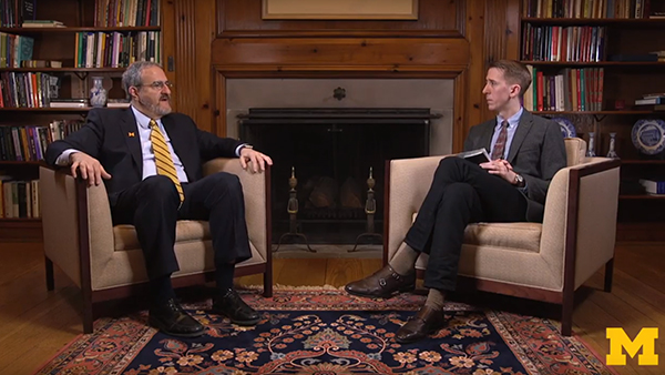 University of Michigan President Mark Schlissel seated speaking with journalist and visiting professor, William Potter.