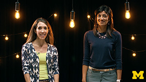Dr. Cathy Goldstein and Dr. Anita Valanju Shelgikar standing in a filming studio smiling at the camera, surrounded by light bulbs