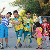 Several children playfully posing for the camera outside