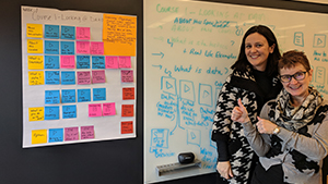 Rebecca Quintana and Brenda Gunderson standing in front of a whiteboard and easel paper page covered in multi-colored sticky notes