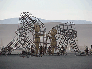 Large wire sculpture of two adults sitting facing away from each other with solid structures of children inside the wire frames reaching out to each other