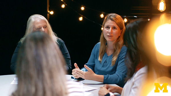 Close-up of a woman speaking to three other women seated at a round table in a filming studio surrounded by light bulbs