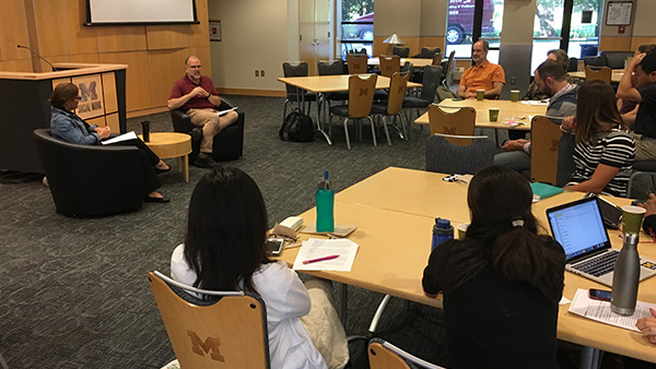 Students and faculty sitting at tables surrounding Dr. Katie Richards-Schuster and Dr. Don Peurach seated facing event attendees.