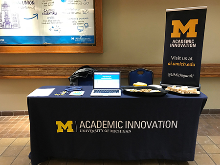 A table covered by an Academic Innovation tablecloth with a laptop on other materials on top and an Academic Innovation banner standing next to the table