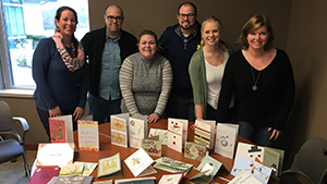 Academic Innovation staff members smiling for the camera standing behind a table of handmade holiday cards
